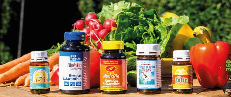 Fünf verschiedene Astaxanthin-Produkte auf einem Tisch mit Gemüseschale im Hintergrund.